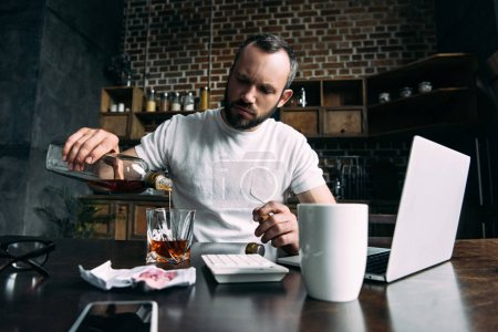 depressed young man pouring whiskey in glass after breakup with girlfriend