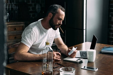 depressed young man smoking cigar and looking at crumpled photo of ex-girlfriend