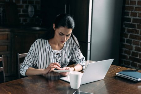 young woman with calculator and laptop counting tax at home on kitchen