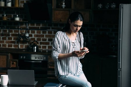 sad young woman sitting on table at kitchen and using smartphone
