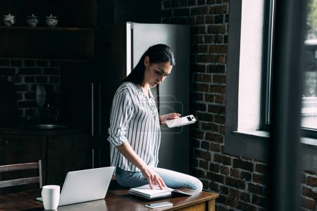 sad young woman with calculator counting tax on kitchen at home