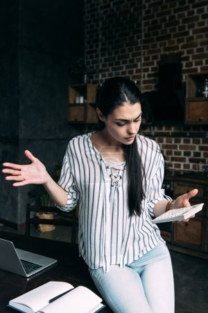 bewildered young woman with calculator counting tax at home and shredding shoulders