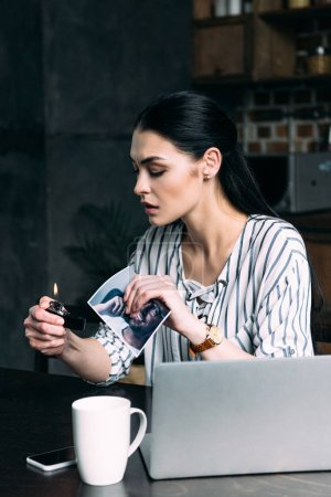depressed young woman burning photo card of ex-boyfriend