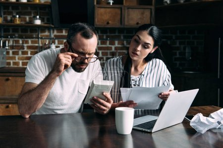 young couple counting bills together at home