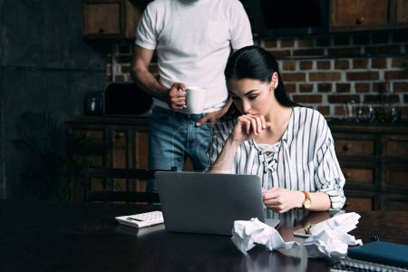 stressed young woman counting bills while her husband standing behind