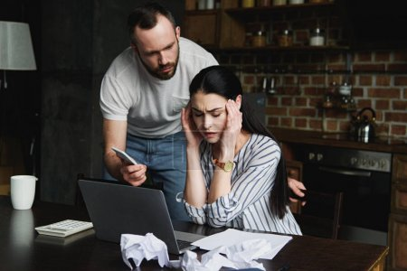 stressed young woman sitting at table with laptop and crumpled papers while her angry husband showing her smartphone screen
