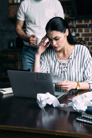 depressed young woman counting bills while her husband standing behind