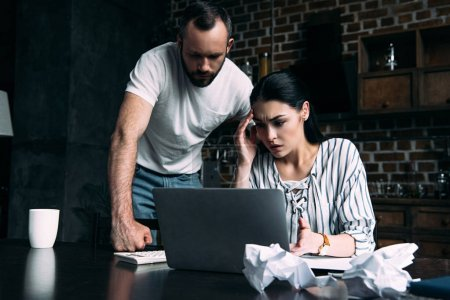 overstressed young couple counting tax at home on kitchen