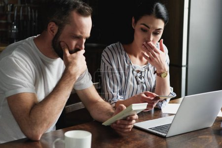 depressed young couple counting tax and bills with laptop and calculator