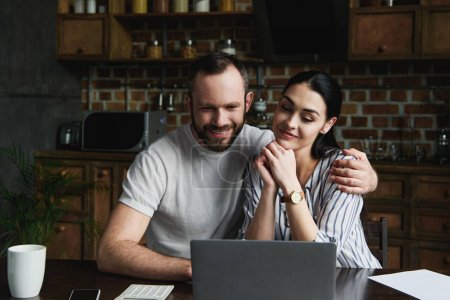 smiling young couple making video call with laptop at kitchen