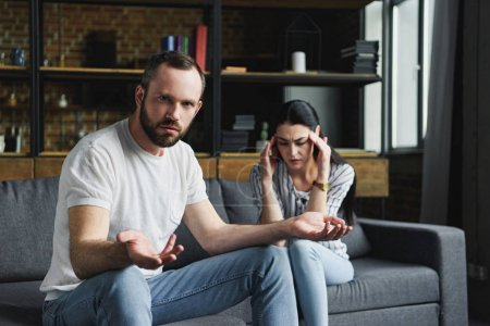 bewildered man looking at camera while his wife sitting on couch depressed