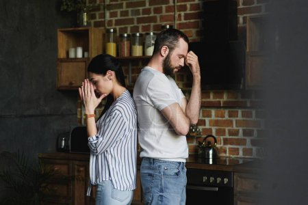 side view of young depressed couple standing back to back after quarrel at home