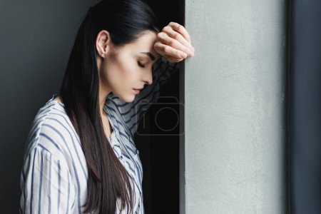 Photo for Side view of depressed young woman leaning on wall with closed eyes - Royalty Free Image