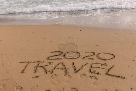 summer beach with 2020 travel lettering on sand near sea