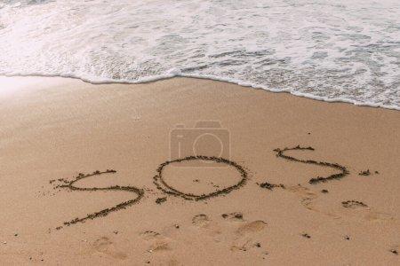 Photo pour Plage d'été avec lettrage sos sur sable près de la mer - image libre de droit