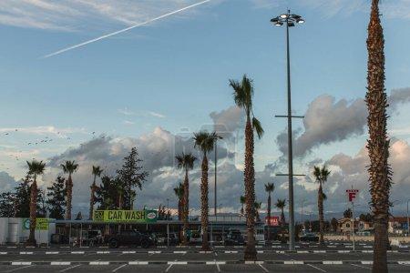 Photo pour PAPHOS, CHYPRE - 31 MARS 2020 : station de lavage près de la voiture et des palmiers verts - image libre de droit