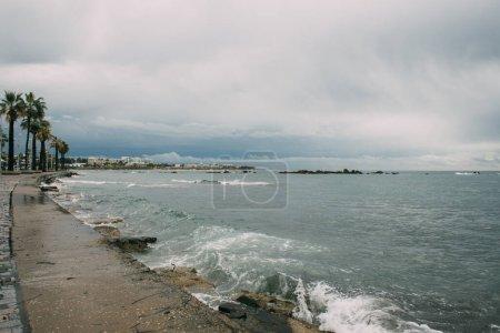 Photo pour Éclaboussure d'eau dans la mer Méditerranée près du rivage avec des palmiers - image libre de droit