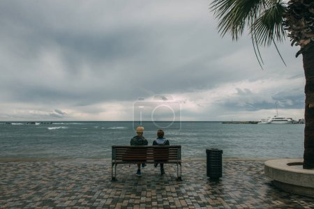 Photo for Back view of two people sitting on bench near sea - Royalty Free Image