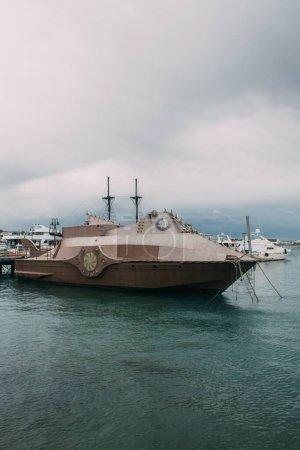 Photo pour Navire rétro près de yachts en mer Méditerranée contre ciel avec nuages - image libre de droit