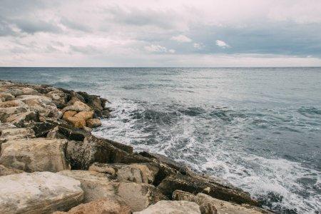 Photo pour Littoral tranquille avec des rochers près de la mer Méditerranée contre ciel nuageux - image libre de droit