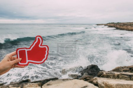Photo for Woman holding thumb up as like near mediterranean sea - Royalty Free Image