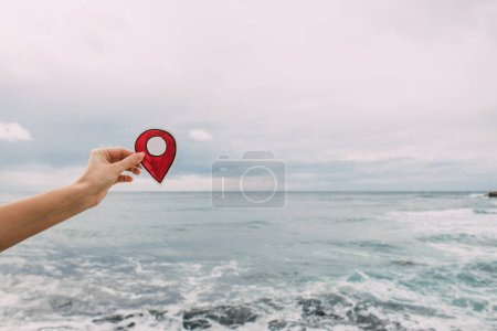 Photo for Cropped view of woman holding paper as location sign near mediterranean sea - Royalty Free Image