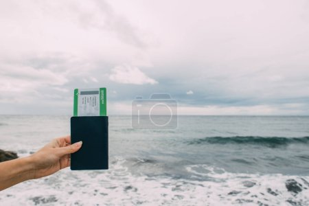 Photo for Cropped view of woman holding passport with flight ticket near sea - Royalty Free Image
