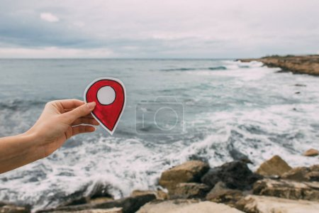 Photo for Cropped view of woman holding red paper as location sign near mediterranean sea - Royalty Free Image