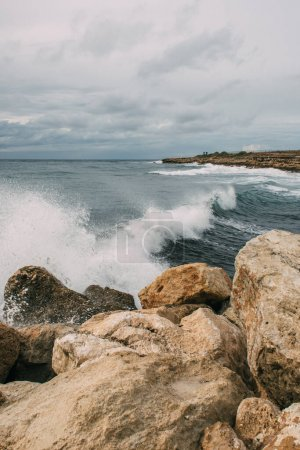 splashes of water from mediterranean sea near rocks