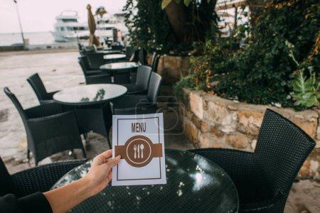 Photo pour Vue recadrée de la femme tenant menu dans le restaurant - image libre de droit