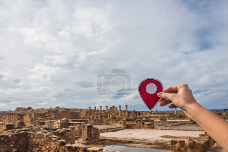 cropped view of woman holding paper as location sign near ancient House of Theseus