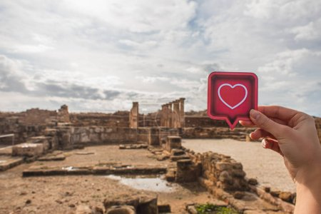 Photo for Cropped view of woman holding paper heart near ancient House of Theseus - Royalty Free Image