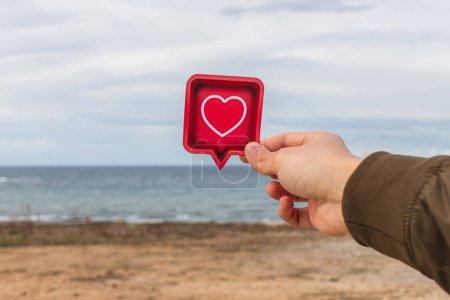 Photo pour Homme tenant coeur de papier près de la mer Méditerranée - image libre de droit