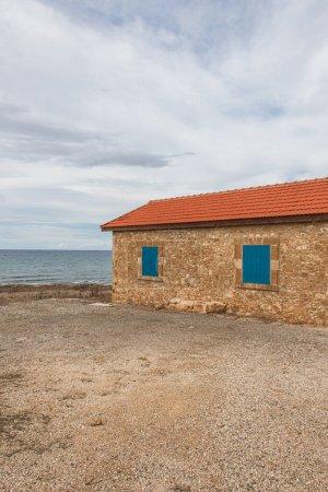 Photo pour Maison avec fenêtres bleues près de la mer Méditerranée contre ciel avec nuages - image libre de droit