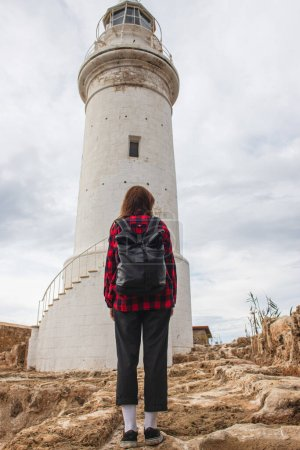 back view of traveler with backpack standing near white lighthouse