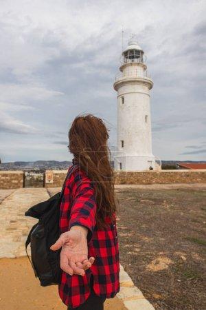 Photo pour Vue arrière de la femme avec la main tendue debout près du phare blanc - image libre de droit