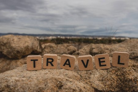 wooden cubes with travel lettering on stones against sky