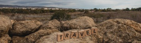panoramic shot of wooden cubes with travel lettering on stones against sky