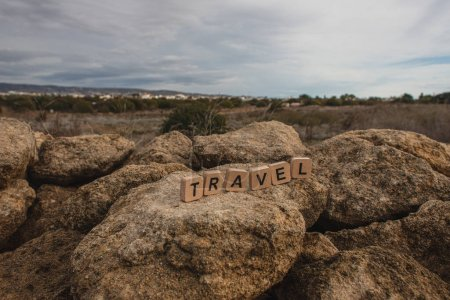 Photo for Wooden cubes with travel lettering on rocks against sky - Royalty Free Image