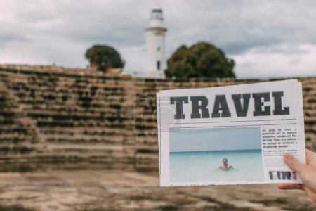 Photo for Cropped view of woman holding travel newspaper near ancient amphitheater and lighthouse - Royalty Free Image