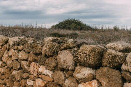 Photo pour Mur avec des pierres près de la pelouse contre le ciel avec des nuages - image libre de droit