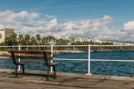 Photo for Wooden bench near blue mediterranean sea in cyprus - Royalty Free Image