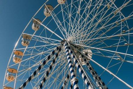 vue à faible angle de la roue ferris contre le ciel bleu en été