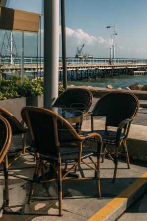 Photo for Sunshine on chairs near table in summer terrace of restaurant near sea - Royalty Free Image