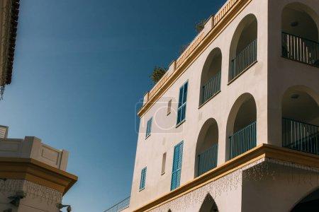 Photo pour Lumière du soleil sur le bâtiment moderne avec des balcons bleus contre le ciel - image libre de droit
