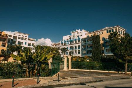 Photo pour Des arbres verts près des maisons modernes contre un ciel bleu - image libre de droit