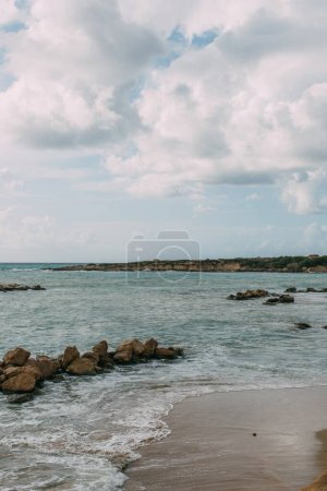 bay with rocks near mediterranean sea against blue sky with clouds