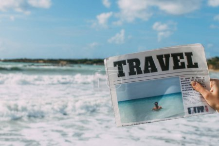 Photo for Cropped view of woman holding travel newspaper near sea - Royalty Free Image