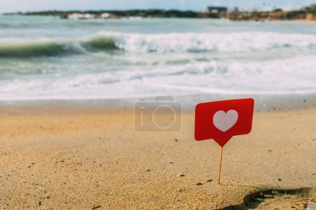 Photo for Red heart on stick on sand near mediterranean sea - Royalty Free Image