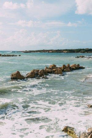 wet stones in mediterranean sea against blue sky